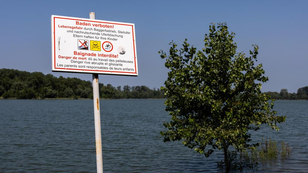 20.07.2021, Baden-Württemberg, Neuried: Ein Schild mit Aufschrift «Baden verboten! - Lebensgefahr» steht am Ufer eines Überflutungsgebietes in der Nähe des Rheins während im Hintergrund ein Baum im Wasser steht. Angesichts der Hochwasser-Katastrophe
