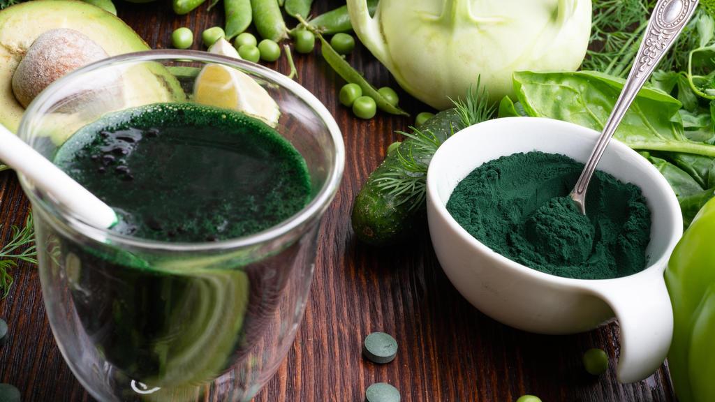 Spirulina-Pulver und -Smoothie vor grünem Gemüse