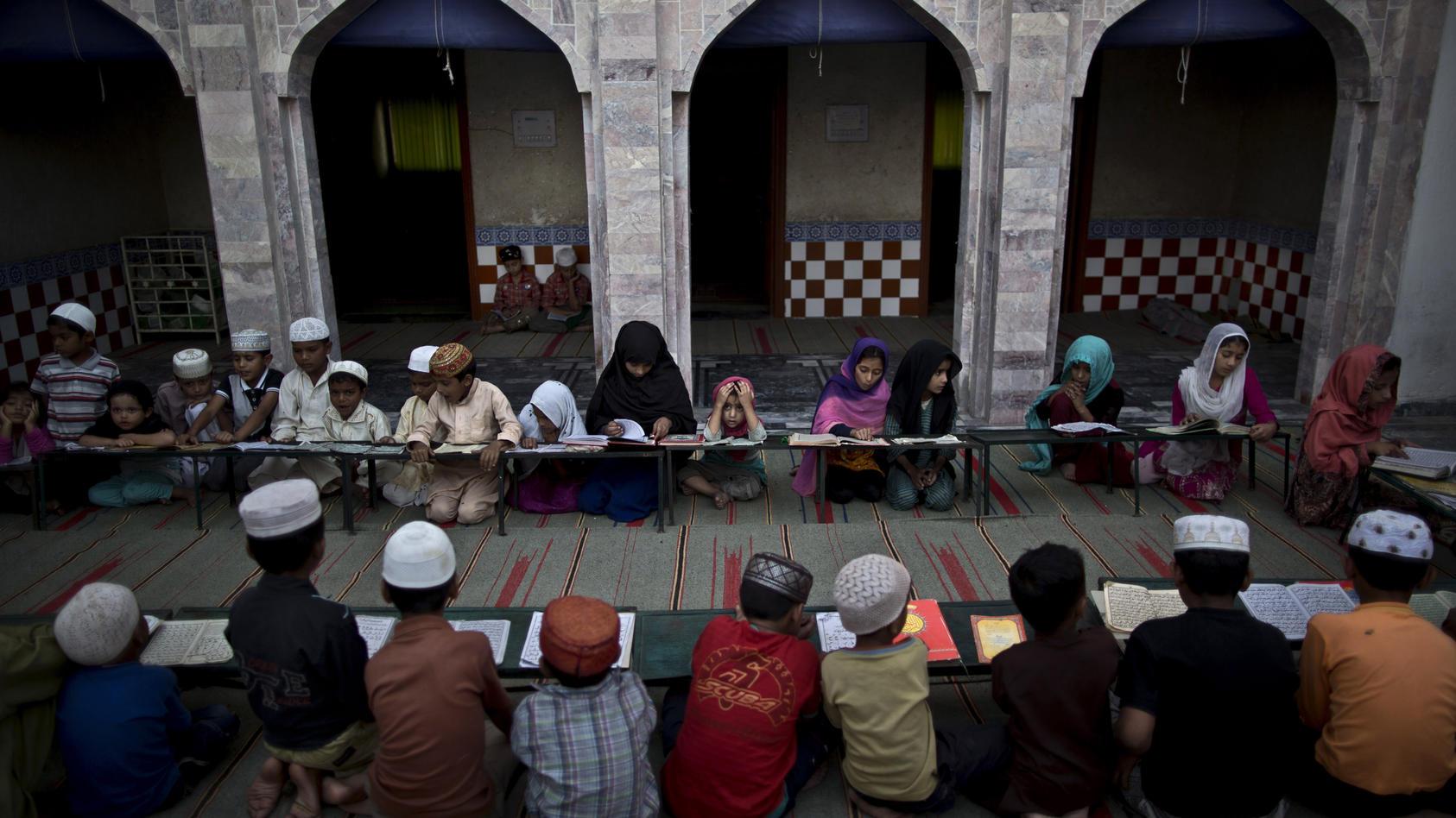 Symbolbild: Islamische Kinder in Pakistan besuchen eine Madrasa (eine religiöse Schule) in Islamabad. (AP Photo/Muhammed Muheisen)