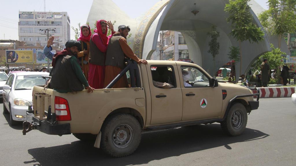 Taliban-Kämpfer sitzen auf der Ladefläche eins Pick-ups.