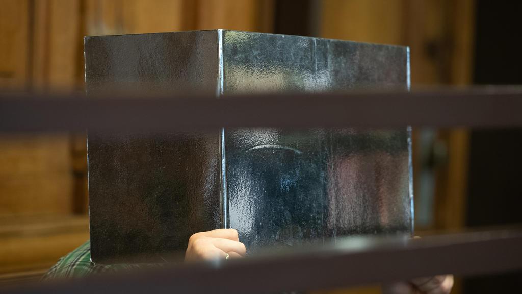 10.08.2021, Berlin: Der Angeklagte sitzt in einem Gerichtssaal und hält sich eine Pappe vor dem Gesicht. Der 41 Jahre alte Lehrer muss sich wegen mutmaßlichem Mord verantworten. Der Beschuldigte soll einen 43-jährigen Mann, den er kurz zuvor über ein