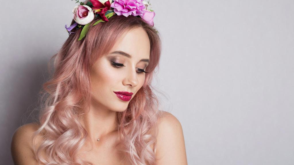 Frau mi roséfarbenen Haaren und Blumenkranz im Haar.