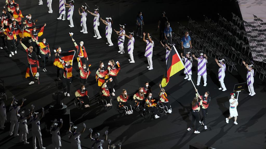 24.08.2021, Japan, Tokio: Paralympics: Eröffnungsfeier im Olympiastadion. Das Team Deutschland kommt zu der Eröffnungsfeier ins Olympiastadion. Die Fahnenträger des Teams Mareike Miller, Rollstuhlbasketball, und Michael Teuber, Paracycling, tragen di