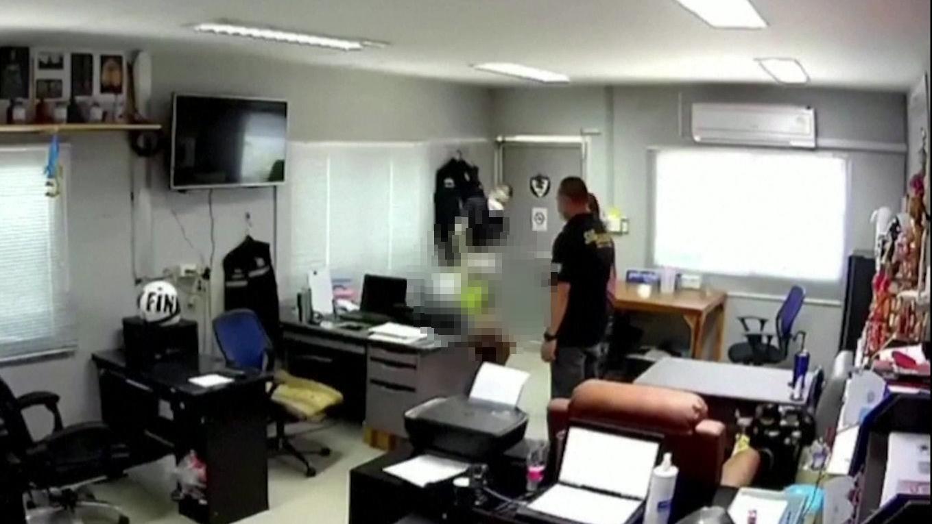 Ausschnitt aus dem Foltervideo, indem thailändische Polizisten einen Mann mit einer Plastiktüte bis zum Tod foltern.