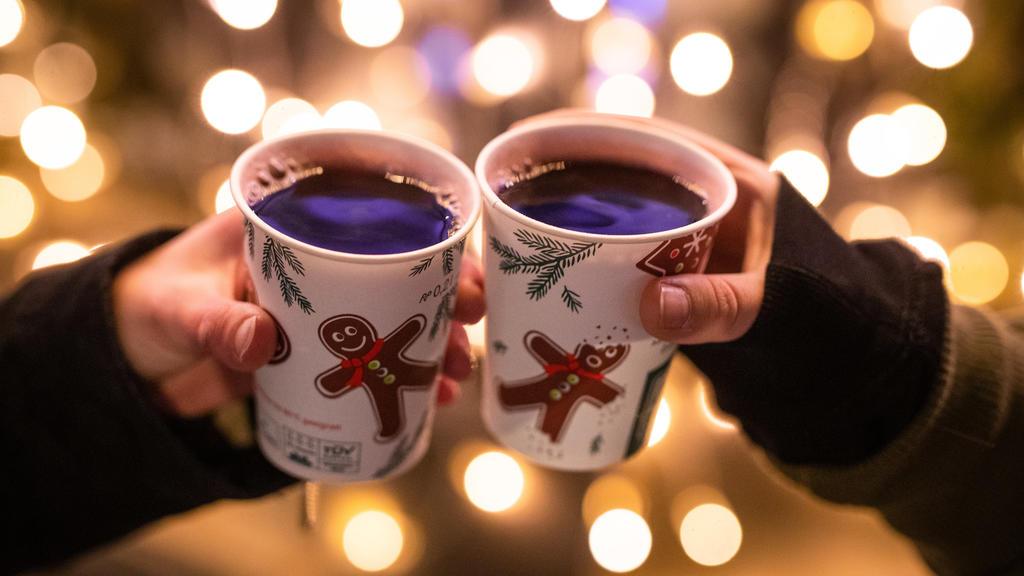 ARCHIV - 07.12.2020, Baden-Württemberg, Stuttgart: Zwei Frauen stoßen mit Glühwein gefüllten Bechern auf dem Weihnachtsmarkt an. (zu dpa «Stuttgarts Weihnachtsmarkt noch unsicher - andere Städte planen fest») Foto: Christoph Schmidt/dpa +++ dpa-Bildf