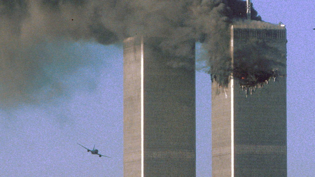 FILE PHOTO: Hijacked United Airlines Flight 175 flies toward the World Trade Center twin towers shortly before slamming into the South tower (L), as the North tower burns, following an earlier attack by a hijacked airliner in New York, U.S., Septembe