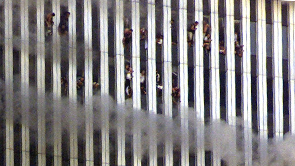 FILE PHOTO: People look out of the burning North tower of the World Trade Center in New York City, New York, U.S. September 11, 2001. REUTERS/Jeff Christensen/File Photo SEARCH 20TH ANNIVERSARY OF THE SEPTEMBER 11 ATTACKS FOR THE PHOTOS