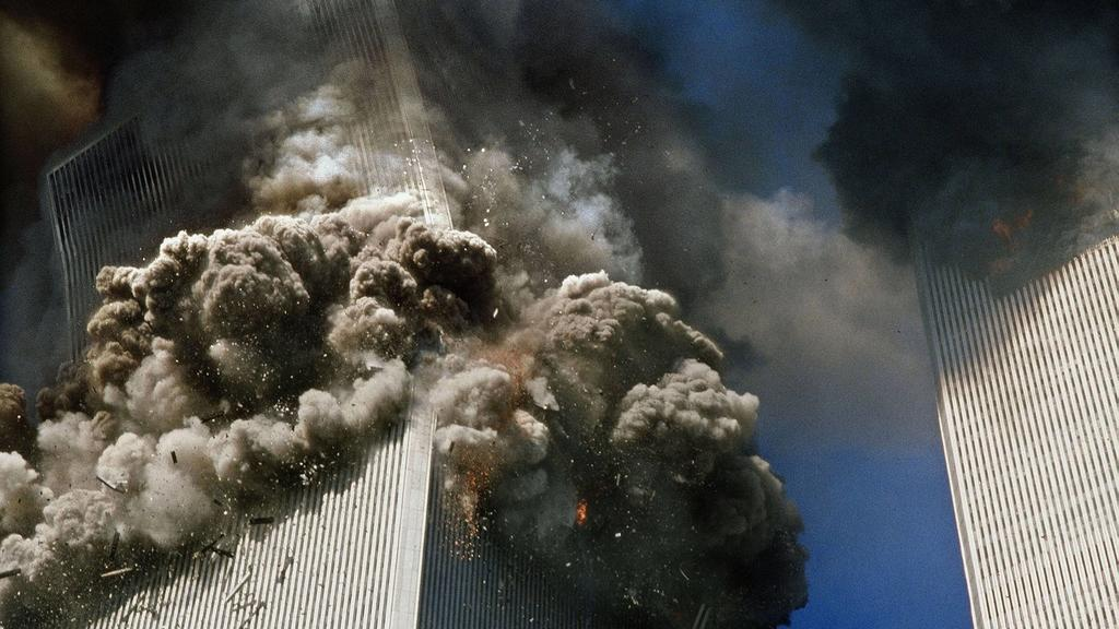 September 11, 2001 - New York, New York, U.S. - The south tower of the World Trade Center, left, begins to collapse in New York Tuesday 9/11. In the most horrifying attacks ever against the U.S., terrorists crashed two airliners into the World Trade