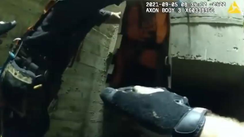 Kräfte der Feuerwehr und Polizei retten den Mann aus dem Gully.