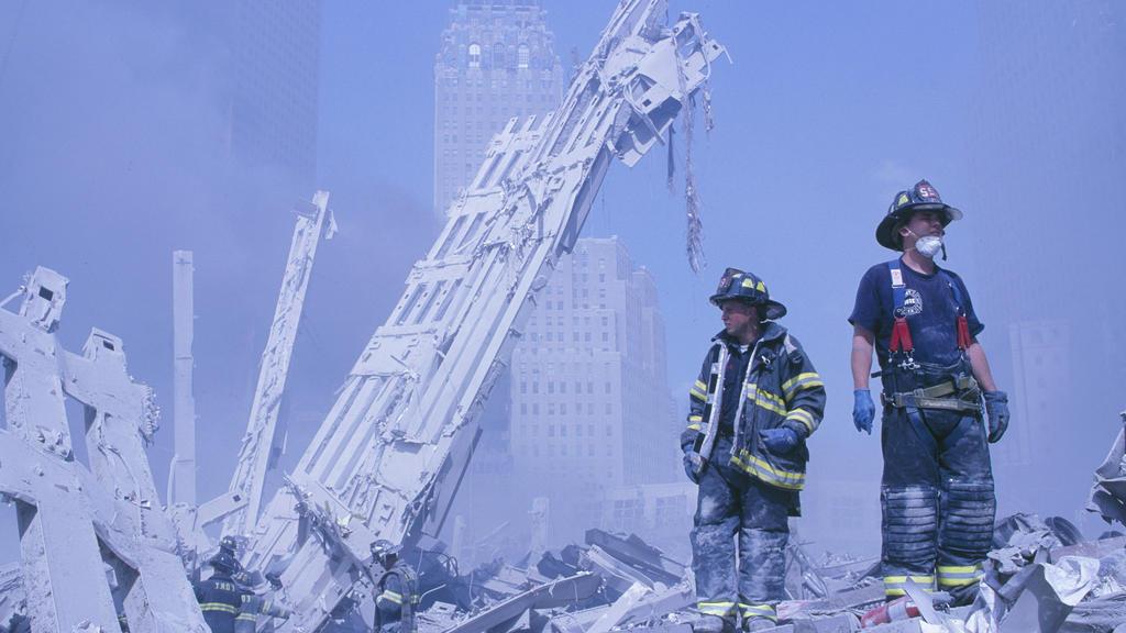 11.09.2001, USA, New York: Feuerwehrleute klettern über die Trümmer des Marriott-Hotels und des in sich zusaamengefallenen zweiten Turms nach dem Terroranschlag auf das World Trade Center. (zu dpa «20 Jahre 9/11: Terroranschläge in den USA») Foto: Ra