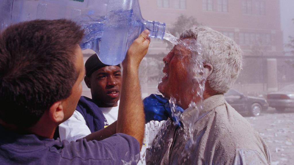 ARCHIV - 11.09.2001, USA, New York: Passanten spülen nach dem Terroranschlag auf das World Trade Center mit Wasser Staub aus dem Gesicht eines Mannes. (zu dpa «20 Jahre 9/11: Terroranschläge in den USA») Foto: Randy Taylor/ZUMA Press Wire Service/dpa