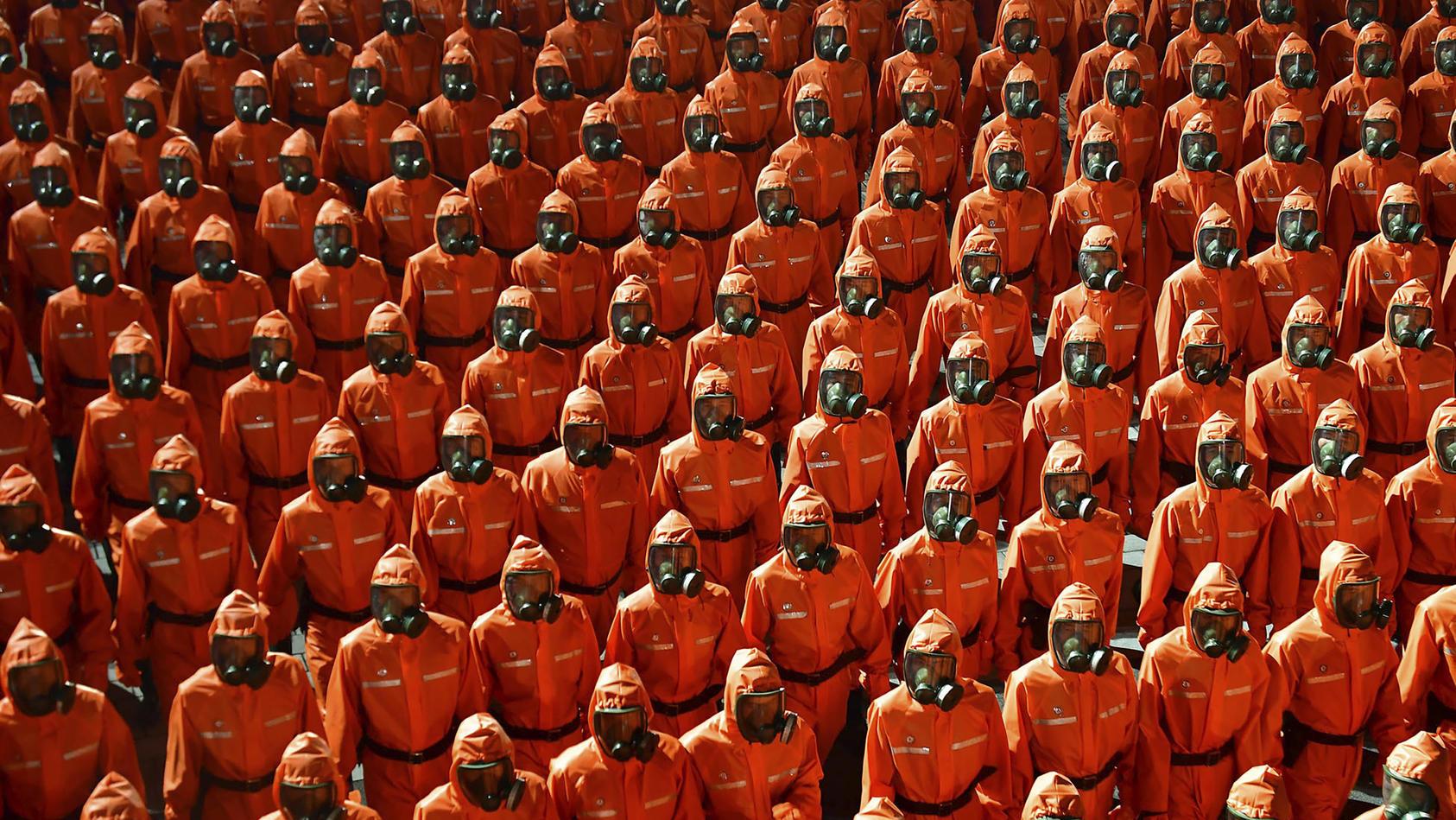 Soldaten tragen bei einer Militärparade in Nordkorea Chemikalienschutzanzüge und Gasmasken.