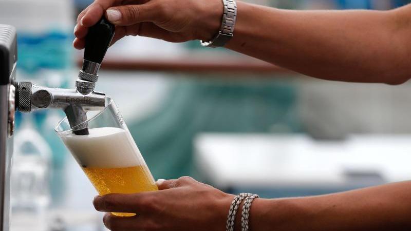 Eine Servicekraft zapft in einer Gaststätte ein Bier. Foto: Axel Heimken/dpa