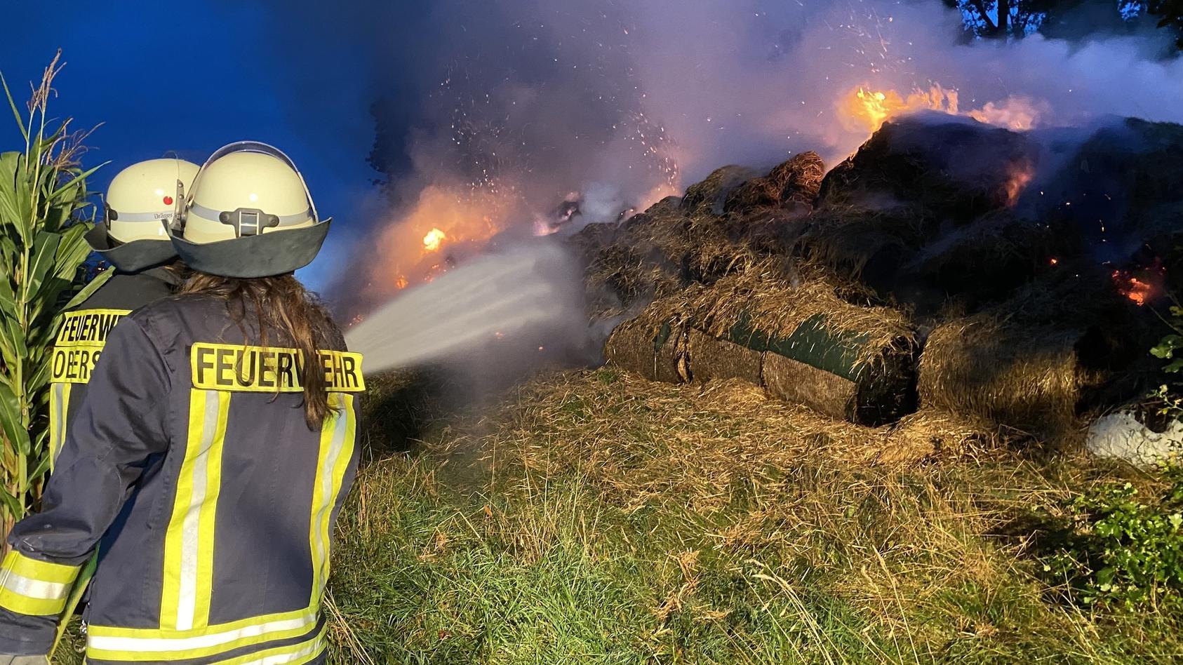 Feuerwehrmänner löschen die brennenden Heuballen. Foto: TVnews-Hessen