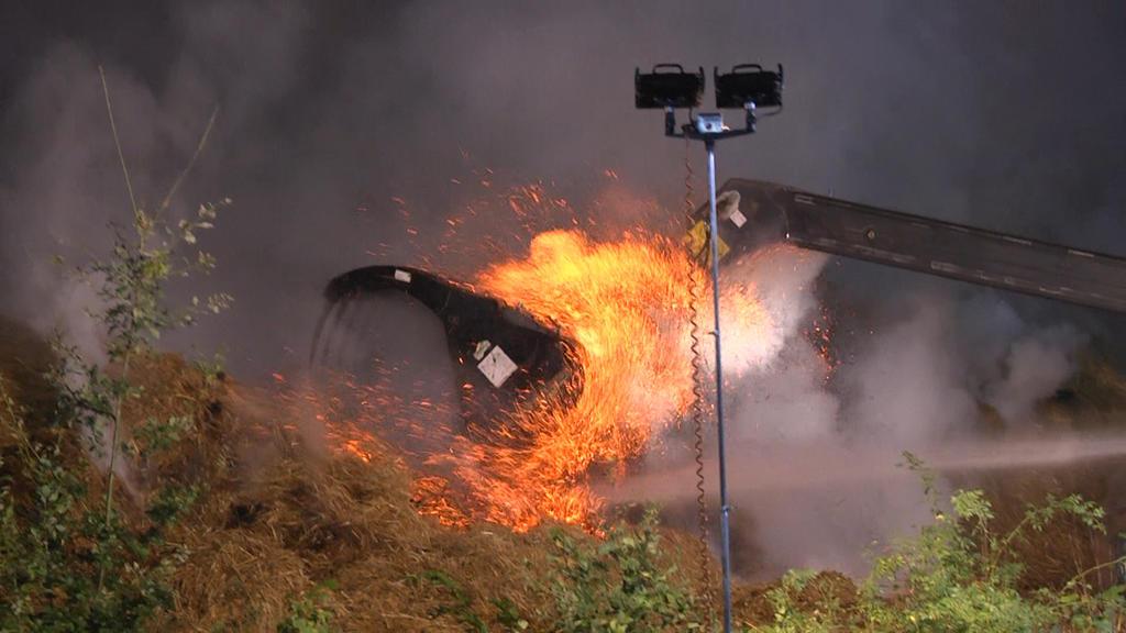 Mit Radladern werden die brennenden Ballen auseinandergezogen.