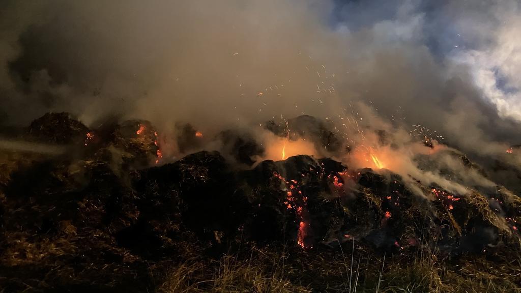 Feuerwehrleute löschen brennende Strohballen
