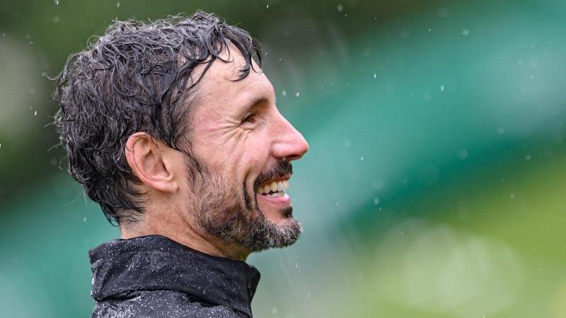 Wolfsburgs Trainer Mark van Bommel lacht auf dem Spielfeld. Foto: Swen Pförtner/dpa/Archivbild