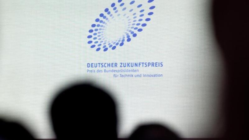 Das Logo vom Deutschen Zukunftspreis ist auf einer Projektionswand zu sehen. Foto: Daniel Karmann/dpa/Archivbild