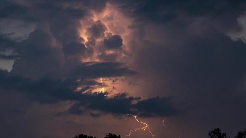 Ein Blitz hellt hinter dunklen Wolken auf. Foto: Fabian Sommer/dpa/Archivbild