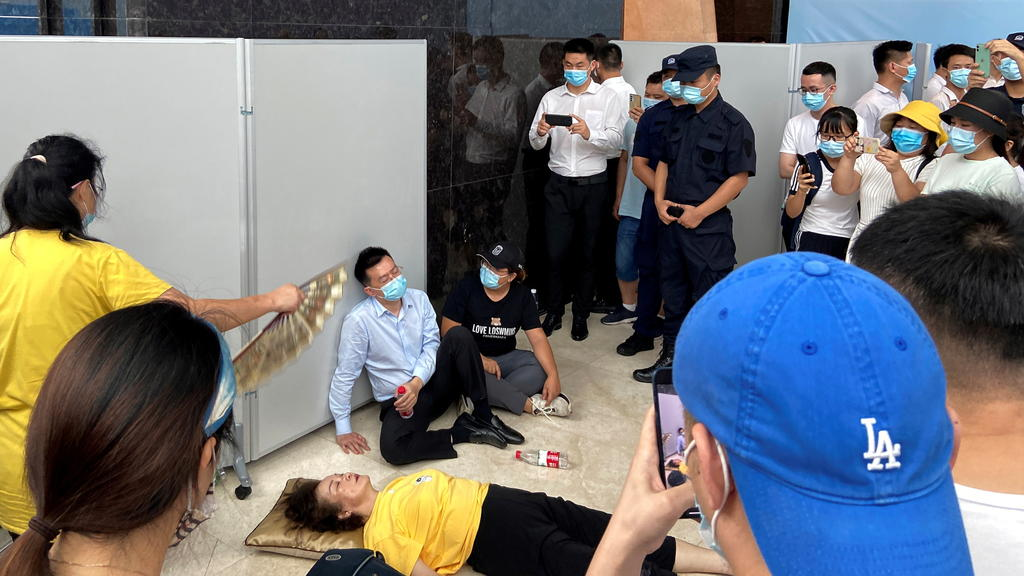 A woman receives aid on the ground next to Du Liang, general manager and legal representative of Evergrande's wealth management division, while people gather to demand repayment of loans and financial products at the Evergrande's headquarters, in She