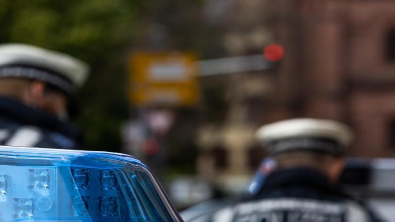 Zwei Polizeibeamte stehen zwischen Einsatzfahrzeugen. Foto: Philipp von Ditfurth/dpa/Symbolbild