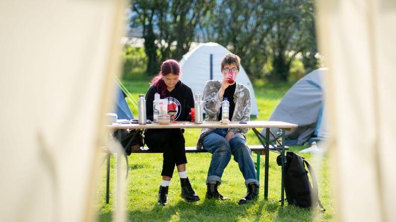 Lina Eichler (r) und Mephisto sitzen vor den Zelten ihres Protestcamps im Regierungsviertel. Foto: Kay Nietfeld/dpa