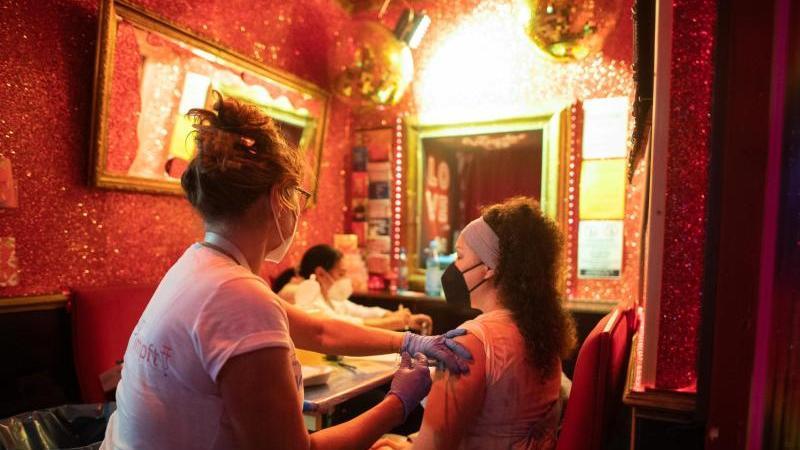 """Eine junge Frau lässt sich im Rahmen der Aktion """"Kiez-Piks"""" in der Bar """"Wunderbar"""" impfen. Foto: Daniel Reinhardt/dpa"""