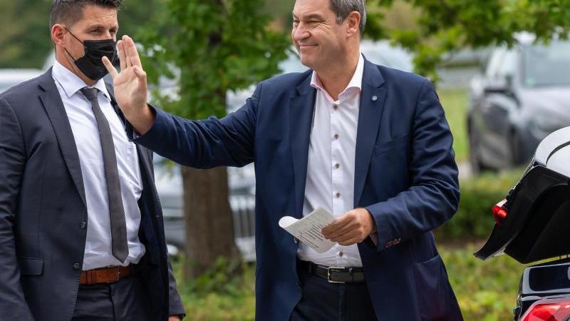 CSU-Chef Markus Söder winkt in Richtung einer Gruppe Menschen. Foto: Peter Kneffel/dpa