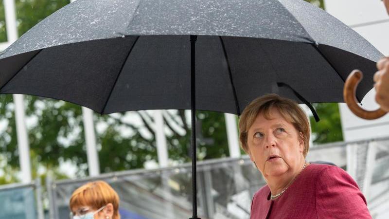 Bundeskanzlerin Angela Merkel verlässt mit einem Regenschirm das Forschungsgebäude. Foto: Peter Kneffel/dpa