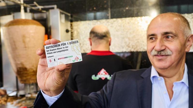 """""""Gutschein für 1 Döner"""" steht auf dem Flyer, den Döner-Besitzer Remzi Kaplan in seinem Imbiss hält. Foto: Annette Riedl/dpa"""