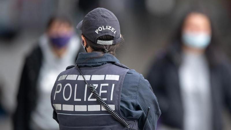 Eine Polizistin blickt zu Passanten mit Masken. Foto: Sebastian Gollnow/dpa/Symbolbild