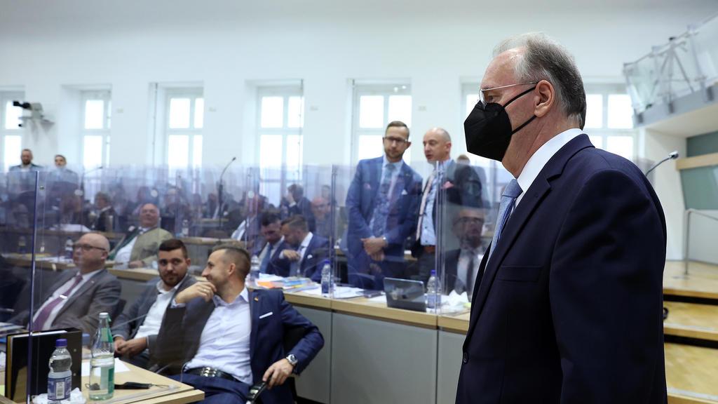 16.09.2021, Sachsen-Anhalt, Magdeburg: Reiner Haseloff (CDU), geschäftsführender Ministerpräsident von Sachsen-Anhalt, betritt vor Beginn des zweiten Wahlgangs den Plenarsaal im Landtag von Sachsen-Anhalt, während im Hintergrund Abgeordnete der AfD-F