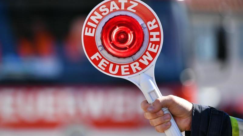 """Ein Feuerwehrmann hält eine Winkerkelle mit der Aufschrift """"Einsatz Feuerwehr"""". Foto: Martin Schutt/dpa-Zentralbild/dpa/Symbolbild"""