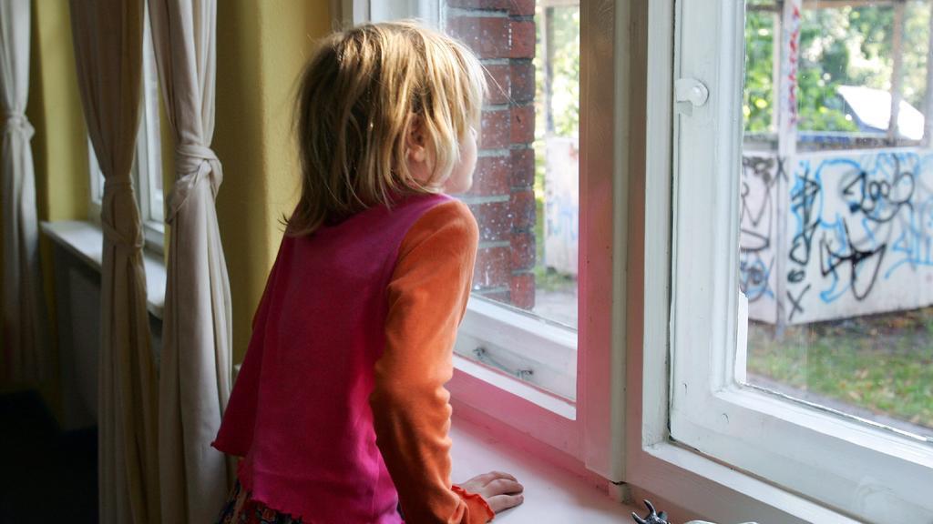 """ARCHIV - Ein kleines Mädchen schaut aus einem Fenster der Kinderstiftung """"Jona's Haus"""" in Berlin (Archivfoto vom 16.09.2006, Illustration zum Thema Kinderarmut). In Deutschland driften Arm und Reich immer weiter auseinander. Die Ungleichheit bei den"""