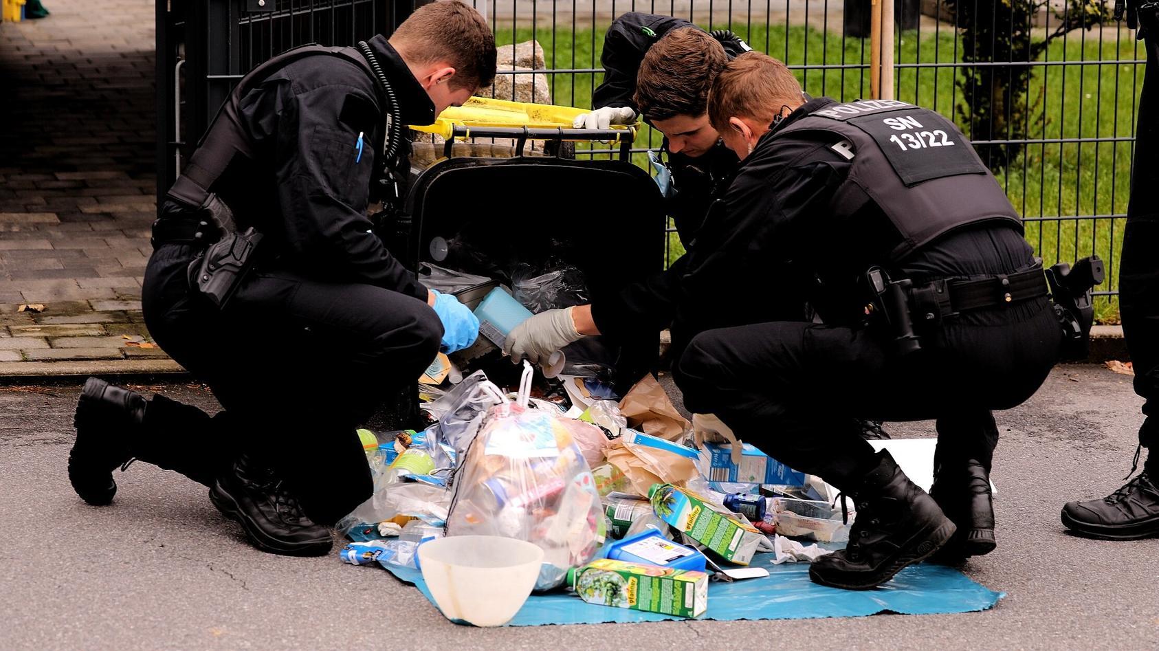 Großröhrsdorf: Polizisten durchsuchen eine Mülltonne nach Hinweisen.