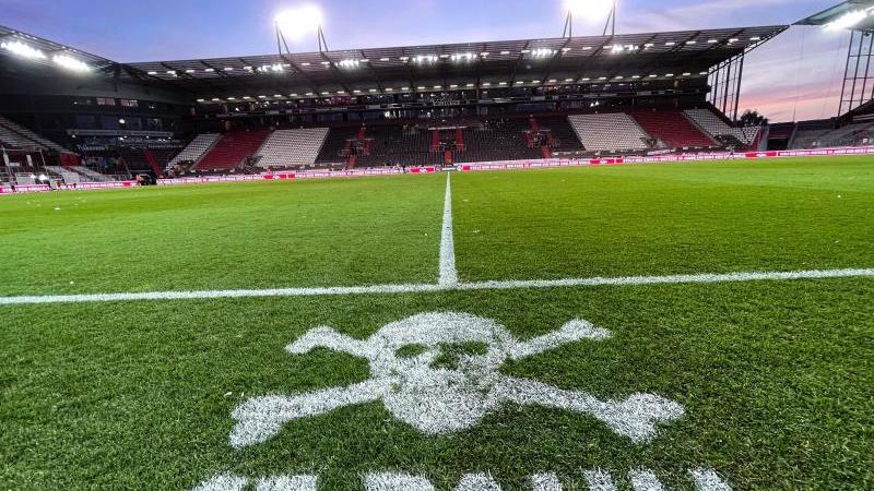 Das Logo von St.Pauli ist an der Mittellinie vor den Trainerbänken auf den Rasen gesprüht. Foto: Christian Charisius/dpa/Symbolbild