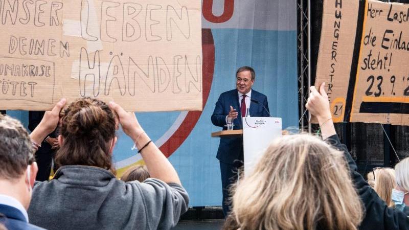 Demonstrierende halten bei einem Wahlkampfauftritt von Armin Laschet Plakate hoch. Foto: Sina Schuldt/dpa