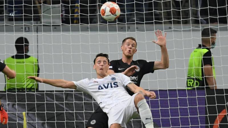 Istanbuls Mesut Özil (l) und Frankfurts Erik Durm kämpfen um den Ball. Foto: Arne Dedert/dpa