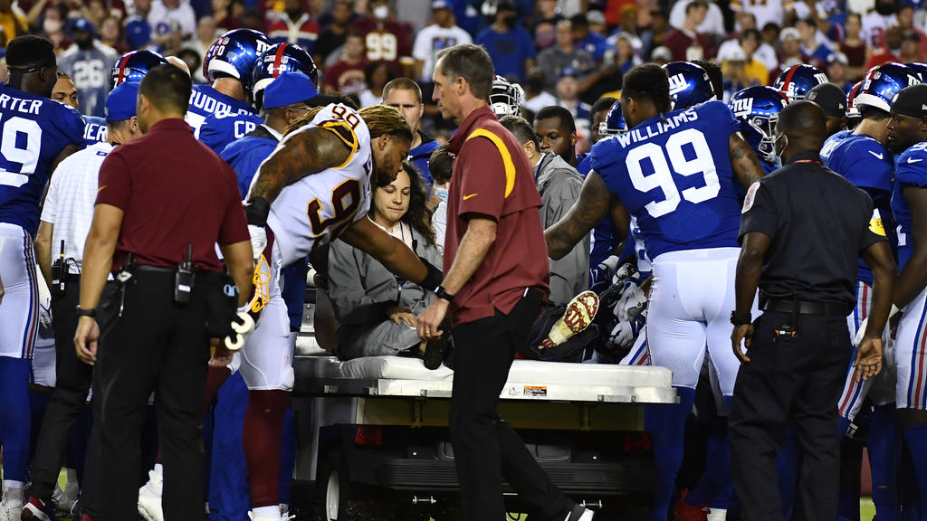 Sep 16, 2021; Landover, Maryland, USA; New York Giants center Nick Gates (65) is consoled by Washington Football Team defensive end Chase Young (99) and New York defensive end Leonard Williams (99) during the first half at FedExField. Mandatory Credi