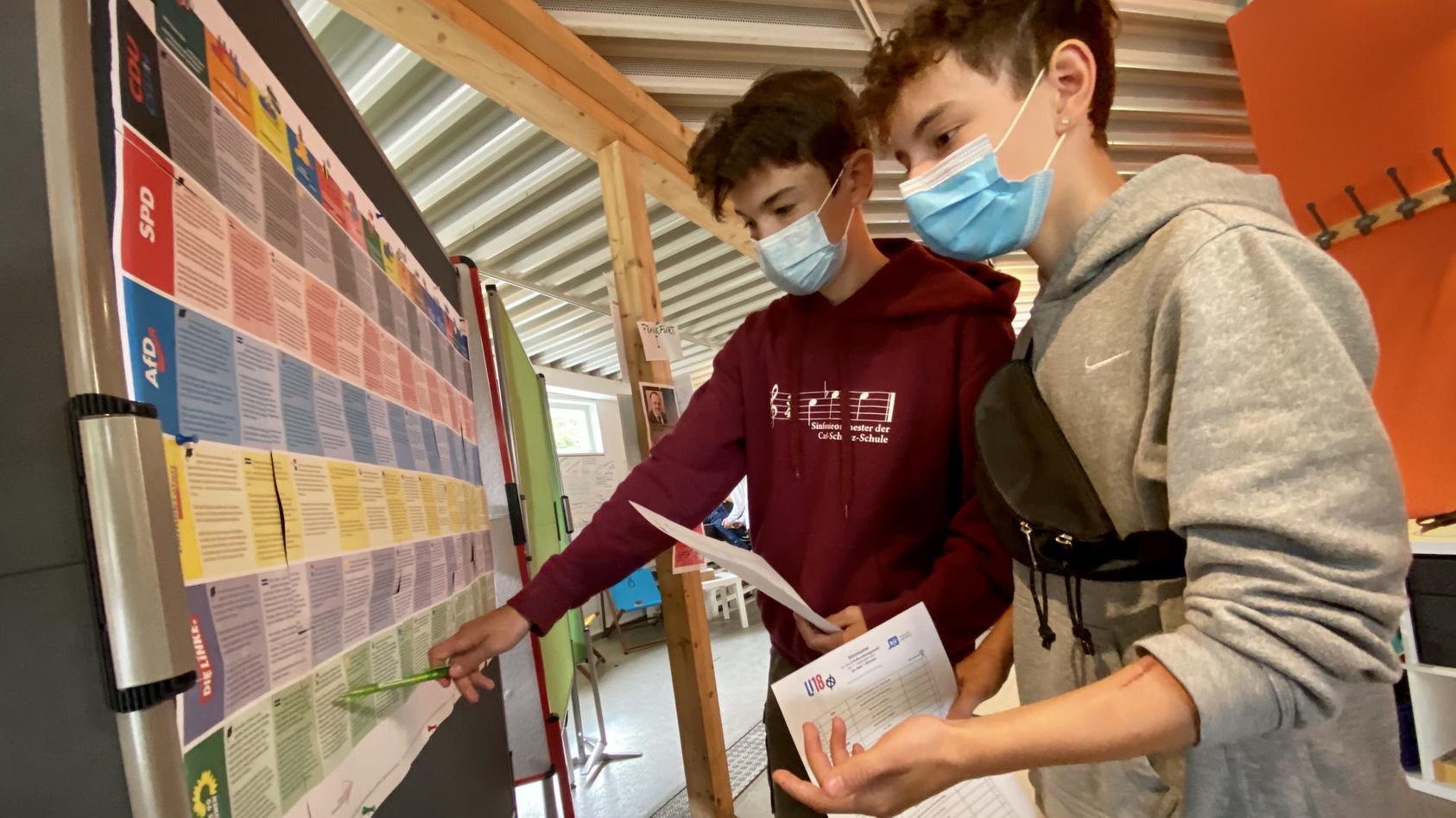 Die beiden Neuntklässler Niko (l.) und Max informieren sich im U18-Wahllokal über die Programme der Parteien.