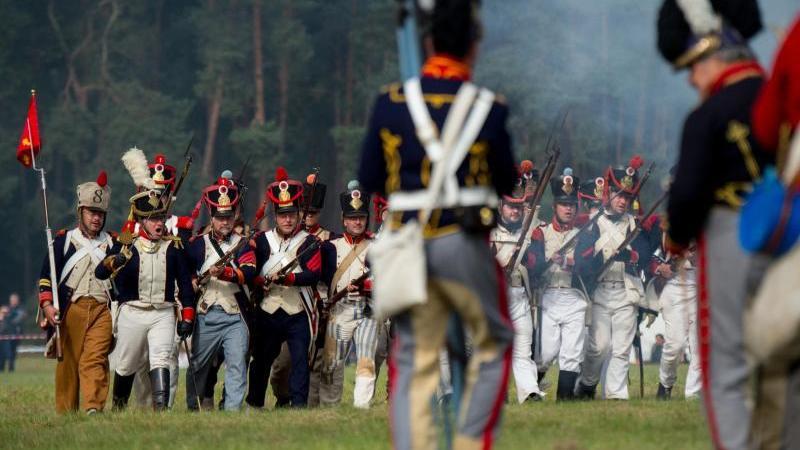 """Als Soldaten verkleidete Darsteller """"kämpfen"""" mit ihren Waffen auf dem Schlachtfeld. Foto: Philipp Schulze/dpa/Archivbild"""