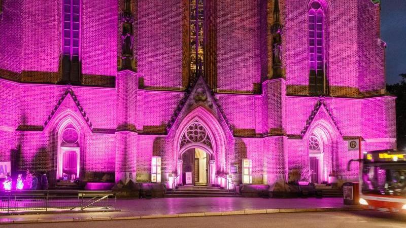 Der Haupteingang der Hauptkirche Sankt Petri wird während einer Beleuchtungsaktion. Foto: Markus Scholz/dpa/Archivbild