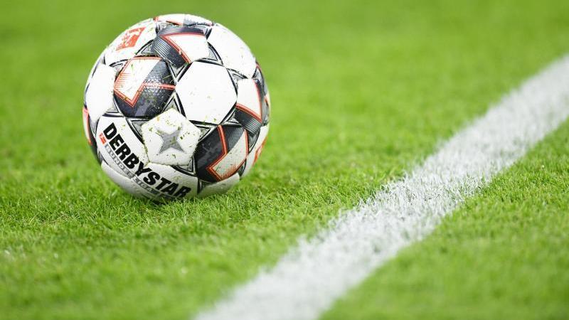 Ein Fußball liegt auf dem Rasen. Foto: Tobias Hase/dpa/Symbolbild