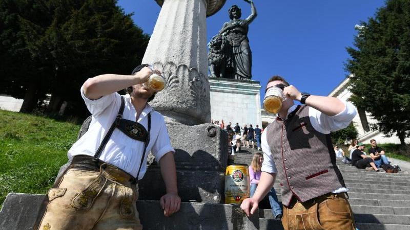Maximilian (l) und Michael trinken pünklich um 12:00 Uhr ihr mitgebrachtes Bier auf der leeren Theresienwiese. Foto: Angelika Warmuth/dpa