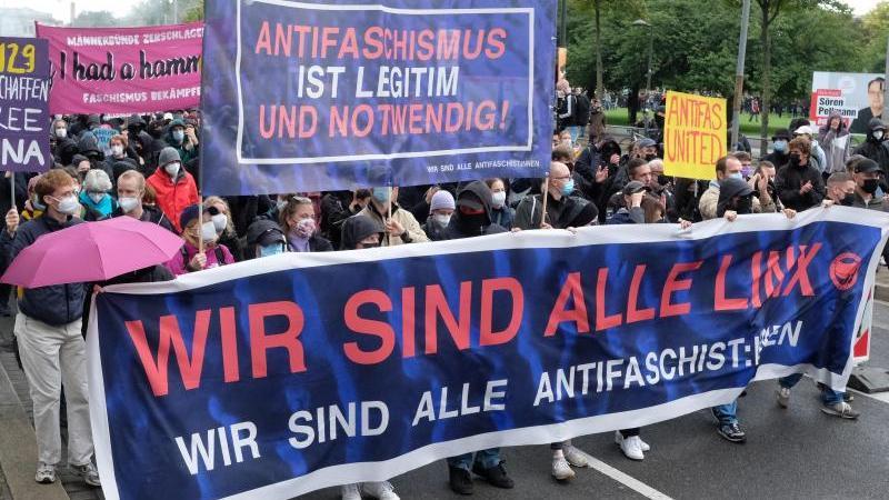 Teilnehmer einer linken Demonstration gehen mit Transparenten eine Straße entlang. Foto: Sebastian Willnow/dpa-Zentralbild/dpa