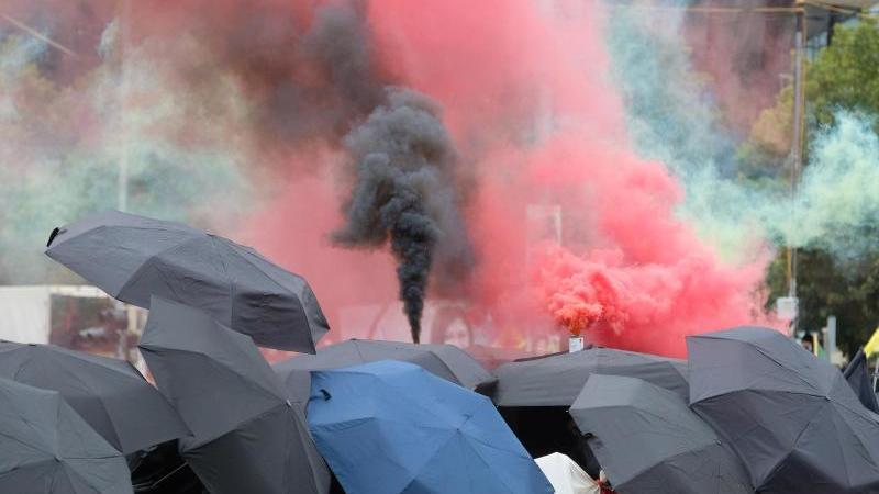 Teilnehmer einer linken Demonstration gehen eine Straße entlang und zünden Pyrotechnik. Foto: Sebastian Willnow/dpa-Zentralbild/dpa