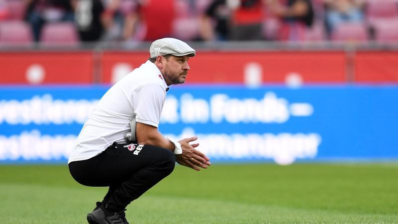 Kölns Trainer Steffen Baumgart hockt vor dem Spiel auf dem Rasen. Foto: Marius Becker/dpa