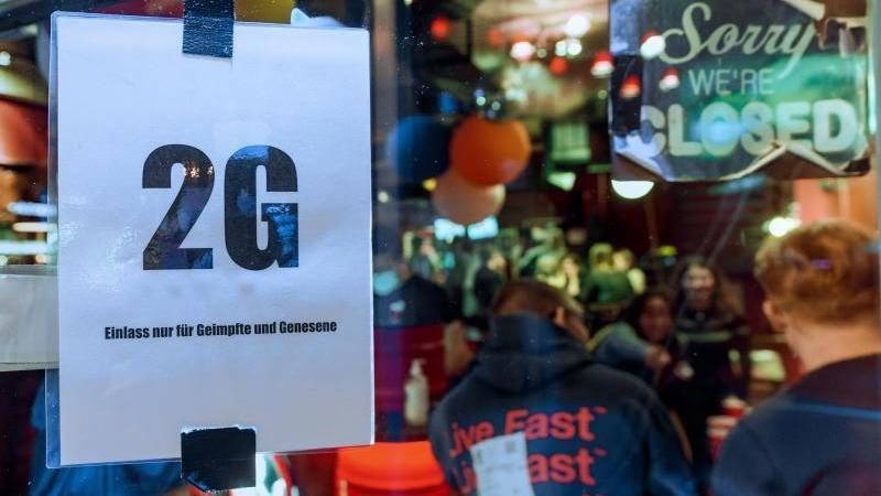 """Im Fenster einer Kneipe hängt ein Zettel mit dem Text """"2G, Einlass nur für Geimpfte und Genesene"""". Foto: Markus Scholz/dpa"""