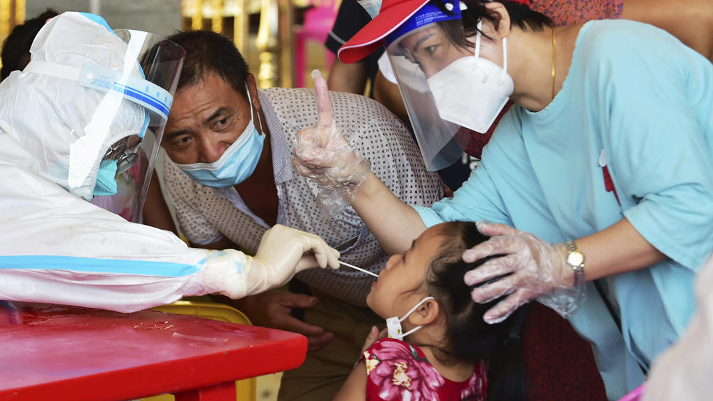In this photo released by Xinhua News Agency, a health worker collects swab sample from a girl for nucleic acid testing in Xianyou county, Putian city, southeastern China's Fujian Province Thursday, Sept. 16, 2021. China has reported another 62 cases