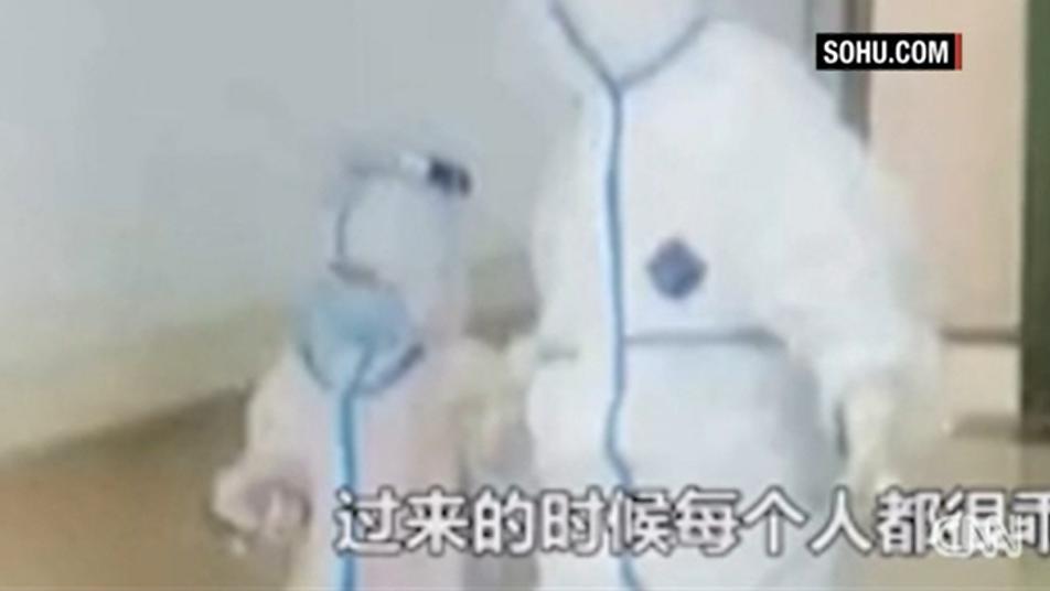 Der Schutzanzug bedeckt den gesamten Körper des kleinen Jungen. Die Krankenschwester bringt ihn auf die Isolationsstation.